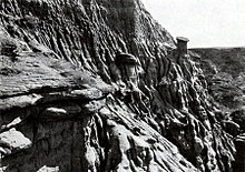 Photograph in black and white of rugged, fissured cliff face