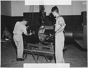 As part of Project Alberta, Commander A. Francis Birch (left) numbers the bomb while physicist Norman Ramsey watches. This is one of the rare photos where the inside of the bomb can be seen.