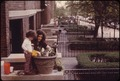 BROOKLYN HOME OWNER PLANTS HER FRONT YARD FLOWER CONTAINER WITH THE HELP OF HER YOUNG SON - NARA - 551730.tif
