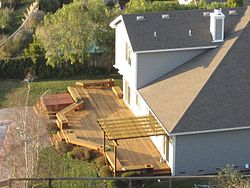 A deck in the backyard of a suburban house.