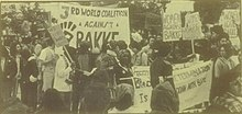 "a monochrome photo of a protest rally.  Many of the protesters are minorities, and have Afro hairstyles.  ""WOMEN AGAINST BAKKE"" is a typical sign being held."