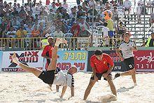 Joueur en train d'effectuer un retourné acrobatique, sous les yeux d'adversaires et de partenaires.