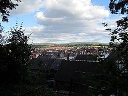 [Foto: Blick vom Waldrand nördlich von Niederkaufungen über den Ort; viele Fachwerkhäuser, viele weiße Häuser, viele rote Ziegeldächer]