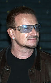 A man with facial hair wearing a leather jacket, a black shirt, an earring, and tinted glasses with a star along the frame.