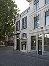 foto van Hoekpand, tevens begin vormend van Veemarktstraat. Gebosseerd gepleisterde lijstgevels met kroonlijst op consoles. Hoog zadeldak met rode pannen