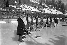 Ice hockey players and staff from two different teams stand together side-by-side in an outdoor ice rink stadium.