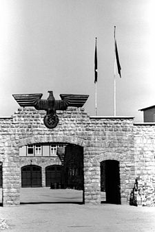 Stone gate topped with a large metal eagle holding a swastika; through the gate a building with two garage doors is visible