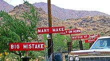 "A set of 6 white-on-red signs with white block text along the side of a road, reading in order ""BIG MISTAKE"", ""MANY MAKE"", ""RELY ON HORN"", ""INSTEAD OF BRAKE"", and, stylized, ""Burma-Shave""."