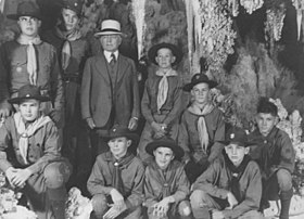 Photograph of Burnham in 1941 celebrating his 80th birthday with several Boy Scouts.  All of them are posing in Carlsbad caverns, the boys are dressed in their Boy Scout uniforms.  Burnham is dressed in a full suit and tie and wearing a white hat.