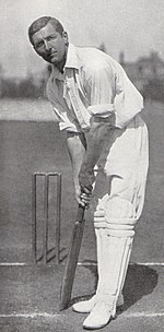 A cricketer in his batting stance.