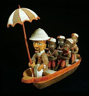 Colon statue - An early Yoruba colon statue from the Tropenmuseum, depicting a European colonial administrator in a canoe rowed by Africans