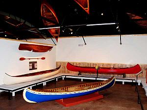Spooner, Wisconsin - An exhibit hall in the Wisconsin Canoe Heritage Museum. Two canoes built by J. H. Rushton, Canton, New York, are along the left wall, and the red canoe was built by B. N. Morris, Veazie, Maine.