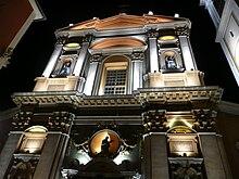 Vue en contre-plongée de nuit d'une façade savamment éclairée de type baroque possédant fronton, décorations et statues.