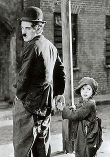 Photographie de Charlot l'air énervé tenant la main à un petit garçon en haillons