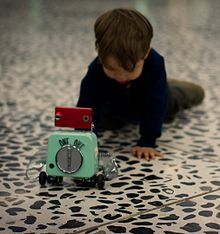 A child appears to crawl toward a tiny toy robot