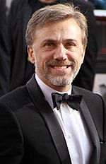 A middle aged man wearing a tuxedo faces forward while smiling.
