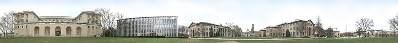 """A panoramic view of Carnegie Mellon University's Pittsburgh campus from the College of Fine Arts Lawn.From left to right: College of Fine Arts, Hunt Library, Baker and Porter Hall, Hamerschlag Hall, University of Pittsburgh's Cathedral of Learning (in the background), Wean Hall and Doherty Hall, Purnell Center, and the University Center. Also visible are """"The Fence,"""" and """"Walking to the Sky"""" sculpture."""