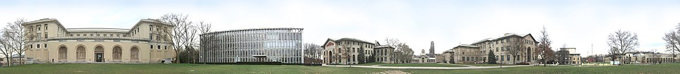 """A panoramic view of Carnegie Mellon University's Pittsburgh campus from the College of Fine Arts Lawn. From left to right: College of Fine Arts, Hunt Library, Baker and Porter Hall, Hamerschlag Hall, University of Pittsburgh's Cathedral of Learning (in the background), Wean Hall and Doherty Hall, Purnell Center, and the Cohon University Center. Also visible are """"The Fence,"""" and the """"Walking to the Sky"""" sculpture."""