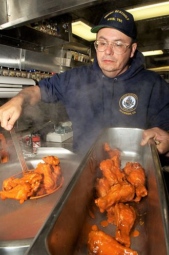 Buffalo wing - A cook preparing Buffalo wings