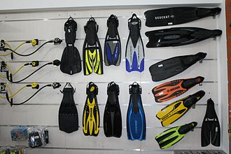 Swimfin - An assortment of fins in a diving shop. Fins on the right are full foot and those in the middle are open heel.