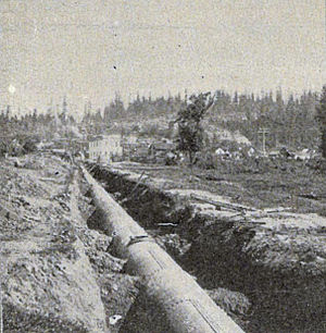 Seattle Public Utilities - Pipe near Renton, Washington to bring Cedar River water to Seattle; this 1900 picture shows pipe newly laid.