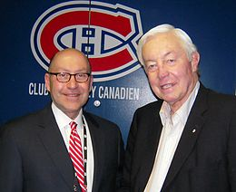 Photo de David Jacobson et Jean Béliveau devant le logo des Canadiens de Montréal