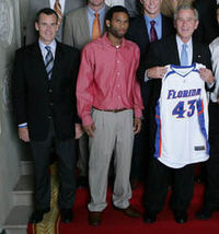 "Florida Gators men's basketball coach Billy Donovan, 42 year-old white man shown in navy blue blazer and tie, and his 2007 NCAA championship team, with former Florida Gator Walter Hodge and  U.S. President George W. Bush holding Florida Gators jersey ""43,"" at the White House."