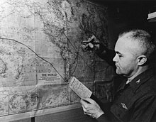 "A balding man holding a small card titled ""Ship's Position"" writes a black line on a map of the Earth."