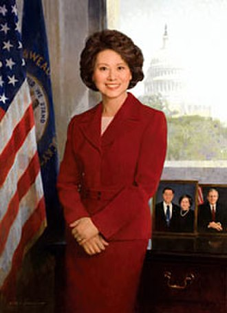 Elaine Chao - Portrait of Elaine Chao by Chen Yanning in the Great Hall of the U.S. Department of Labor's Frances Perkins Building. It features the American flag, the Kentucky state flag, the U.S. Capitol, and photos of her husband, Mitch McConnell, and her parents, James and Ruth Chao.