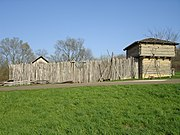 A wooden stockade fronted by a wall of vertically-placed logs and a corner blockhouse