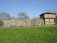 Ein hölzerner Palisaden vor einer Wand aus vertikal angeordneten Baumstämmen und einem Eckblockhaus