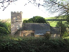 Stone building with tiled roof and square tower, surrounded by vegetation.