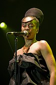 An Afro-American woman singing through a microphone.