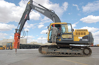 Jackhammer - An excavator-mounted hydraulic jackhammer being used to break up concrete.