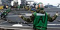 Flickr - Official U.S. Navy Imagery - A Sailor signals for Sailors to set up the barricade during flight deck drills..jpg