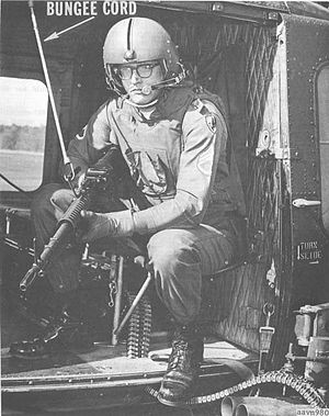 Door gunner - A U.S. Army Vietnam-era door gunner (c. 1966) is shown manning his duty position on a UH-1B/C helicopter gunship, with a 'bungee cord' securing his M60 machine gun to the aircraft cabin doorway.