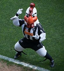 A person costumed as a rooster in a football uniform