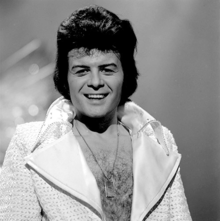 Black-haired man with a hairy chest, wearing a shiny jacket open to the waist, with large lapels, smiles towards the camera.