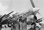 Ground crews loading 3-inch rocket projectiles onto a Hawker Typhoon Mk IB of No. 247 Squadron RAF at B2-Bazenville, Normandy, 15 June 1944. CL157.jpg