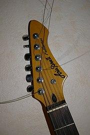 A cabeça de uma guitarra elétrica com seis tarrachas em linha