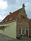 foto van Huis met bakstenen puntgevel met waterlijsten en uitgekraagde toppilaster met sieranker