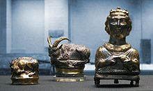 3 silvery objects, two of recumbent animals (One with prominent horns) and a bust