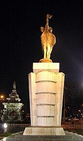 Kamienny posąg niosących pochodnie widziany nocą.  W tle fontanna z białą podstawą