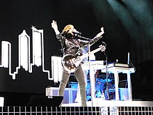 A female blond performer playing an electric guitar on stage. She is wearing black jacket and pants. The backdrops behind her display a numberof tall buildings. The stage is illuminated by a number of halogen lights from the ceiling.