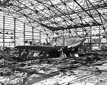 A damaged airplane in a destroyed hangar