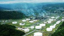 Aerial photo of oil refinery: many white storage tanks and smoke amid greenery