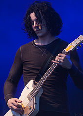 Jack White performing with a white guitar