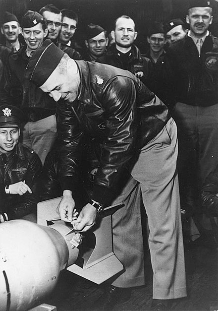 "Lieutenant Colonel Doolittle wires a Japanese medal to a bomb, for ""return"" to its originators. James H Doolittle medal bomb.jpg"