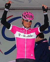 A man in a pink helmet wearing a pink top with black arm-warmers and gloves. He has hands above his head