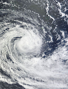Satellite image of a rather disorganized tropical cyclone, with ragged banding features and a disorganized center of circulation.